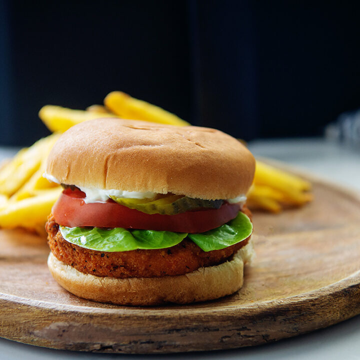 Chicken sandwich on a wooden plate in front of a pile of fries