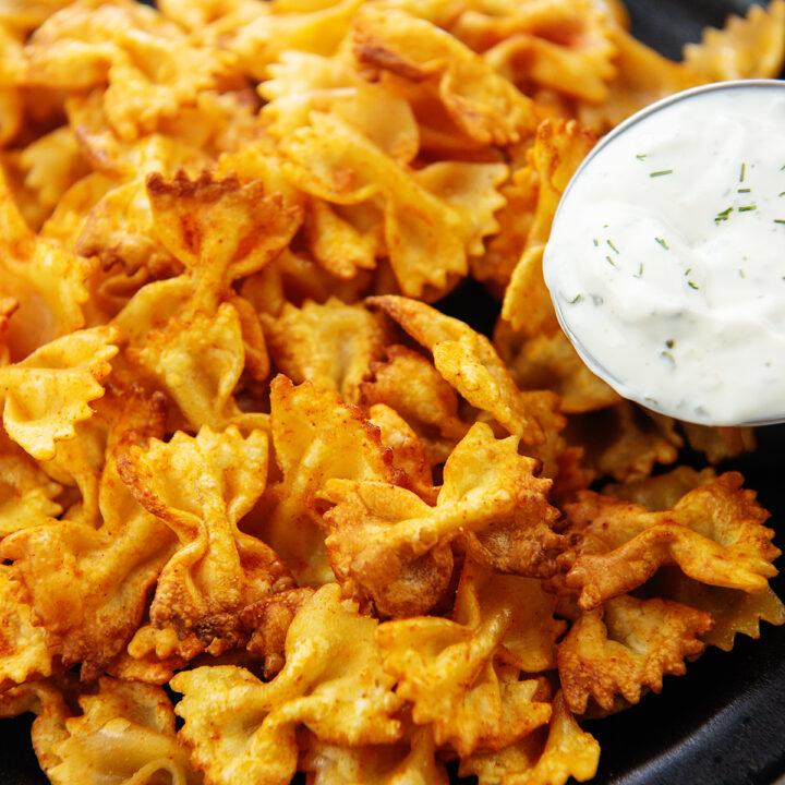 TikTok pasta chips on black plate next to dip.