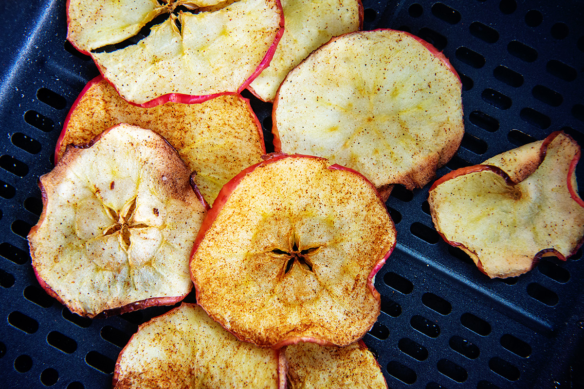 Cinnamon topped apple chips in an air fryer basket