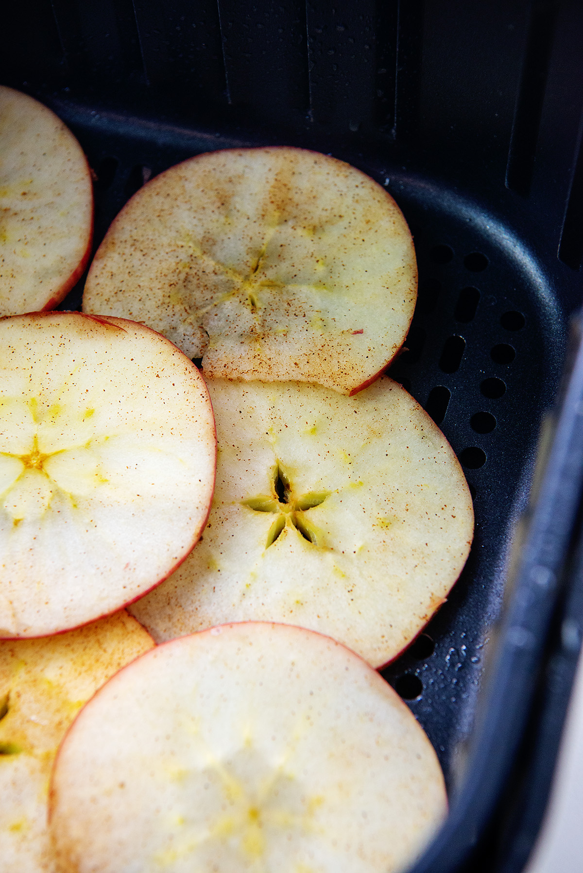 Sliced apples in an air fryer basket with cinnamon on them.
