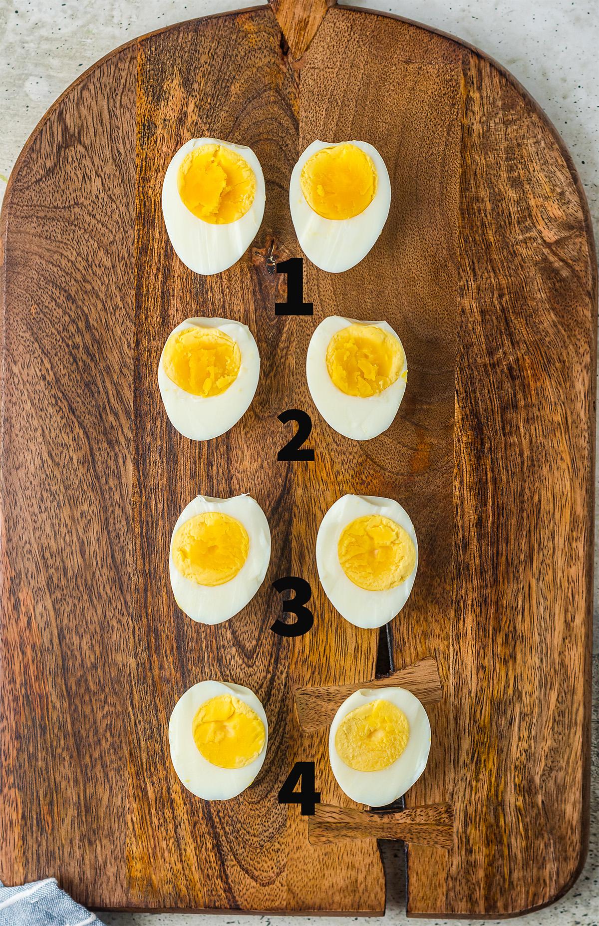 Four eggs cut in half on a wooden cutting board