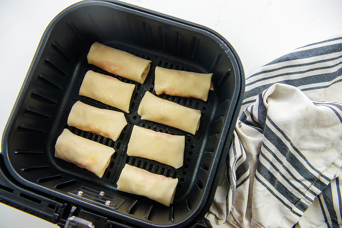 Raw egg rolls lined up in an air fryer basket