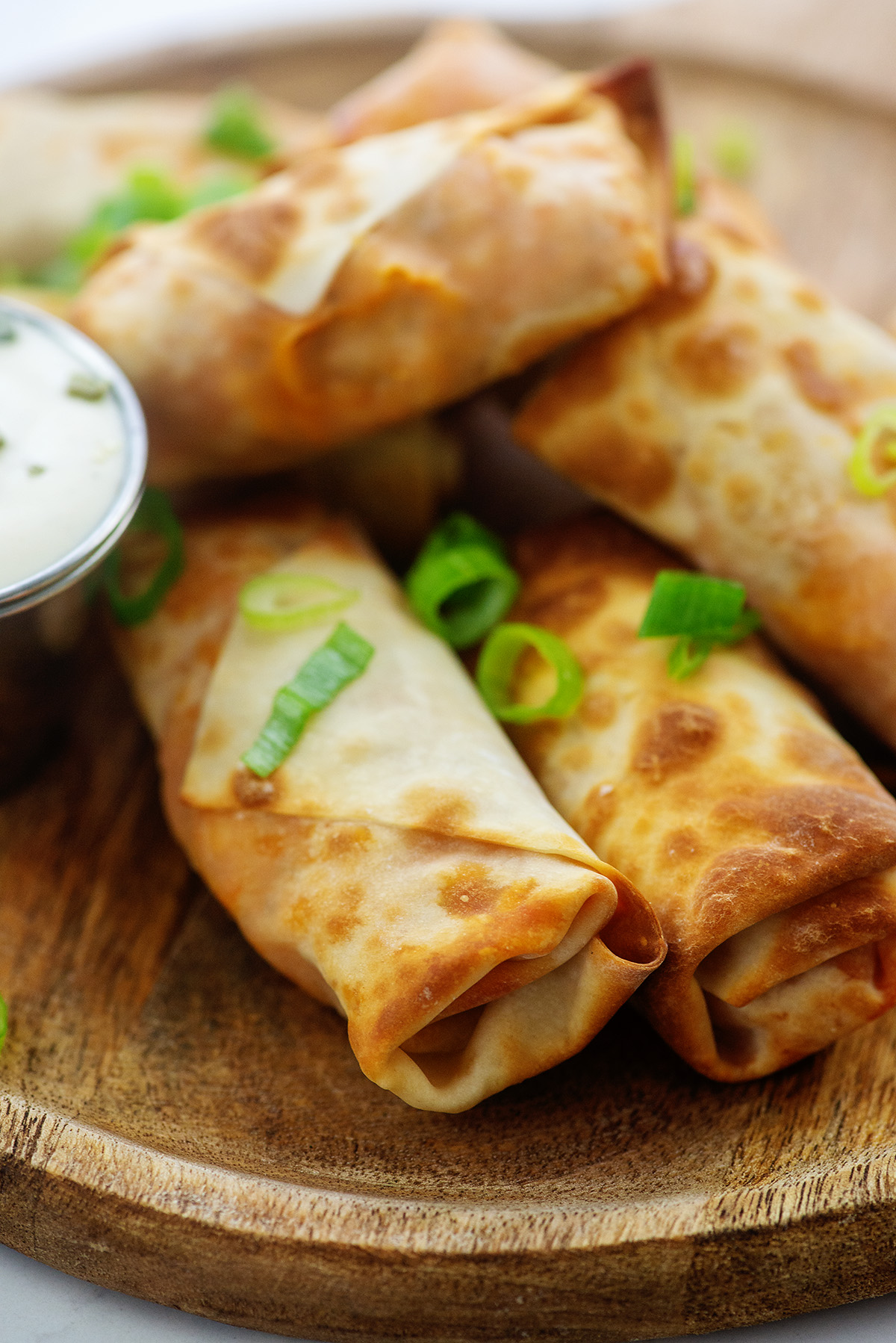 Close up of egg rolls on a wooden plate topped with green onions