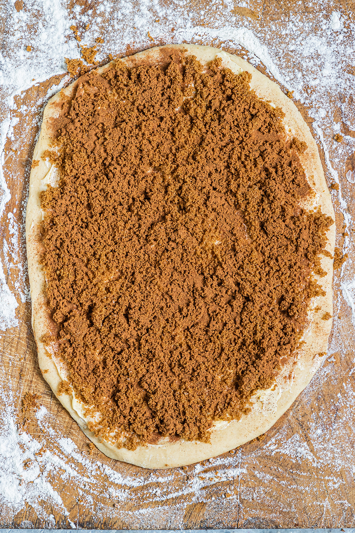 raw dough and a cinnamon mixture spread out on a countertop
