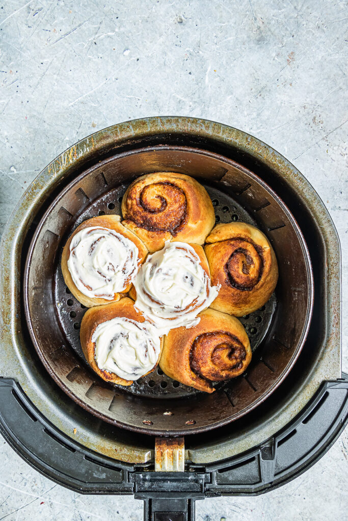 Overhead view of 3 iced and non iced cinnamon rolls in an air fryer basket