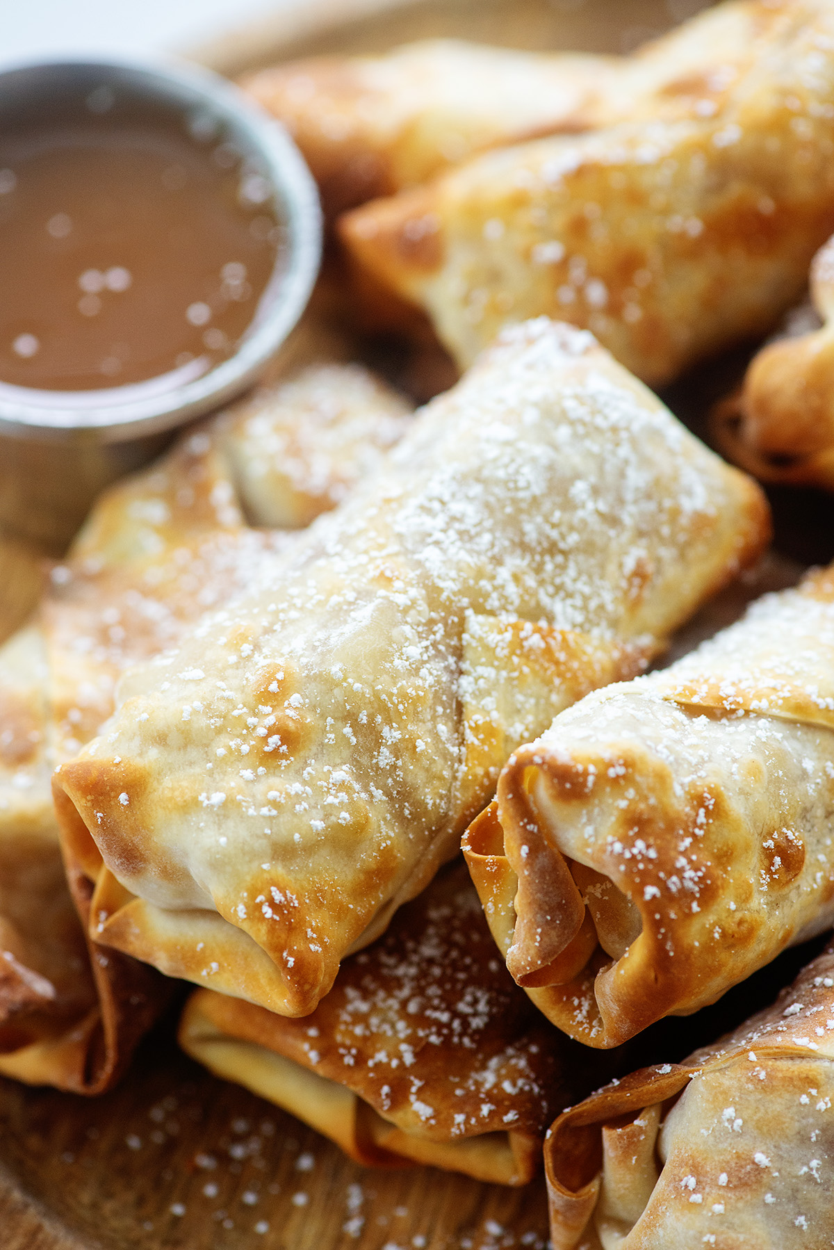 Cose up of stackd egg rolls with powdered sugar on them