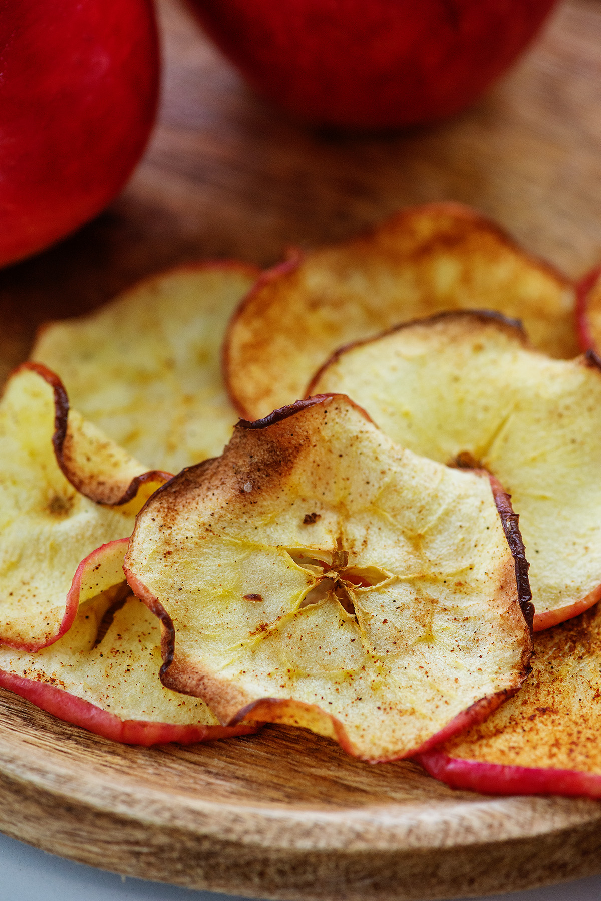 Close up of apple chips on a wooden plate