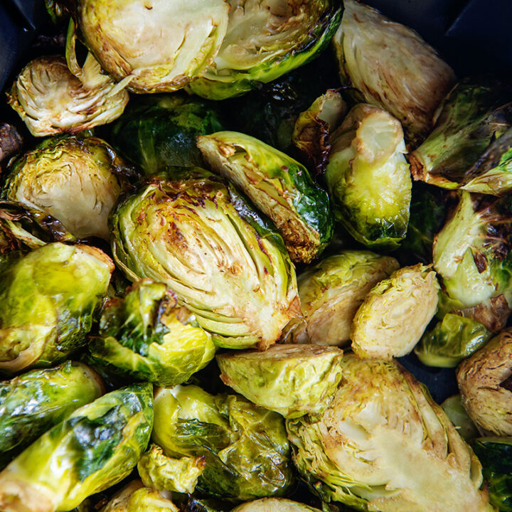 Close up of Brussels sprouts piled up in an air fryer basket