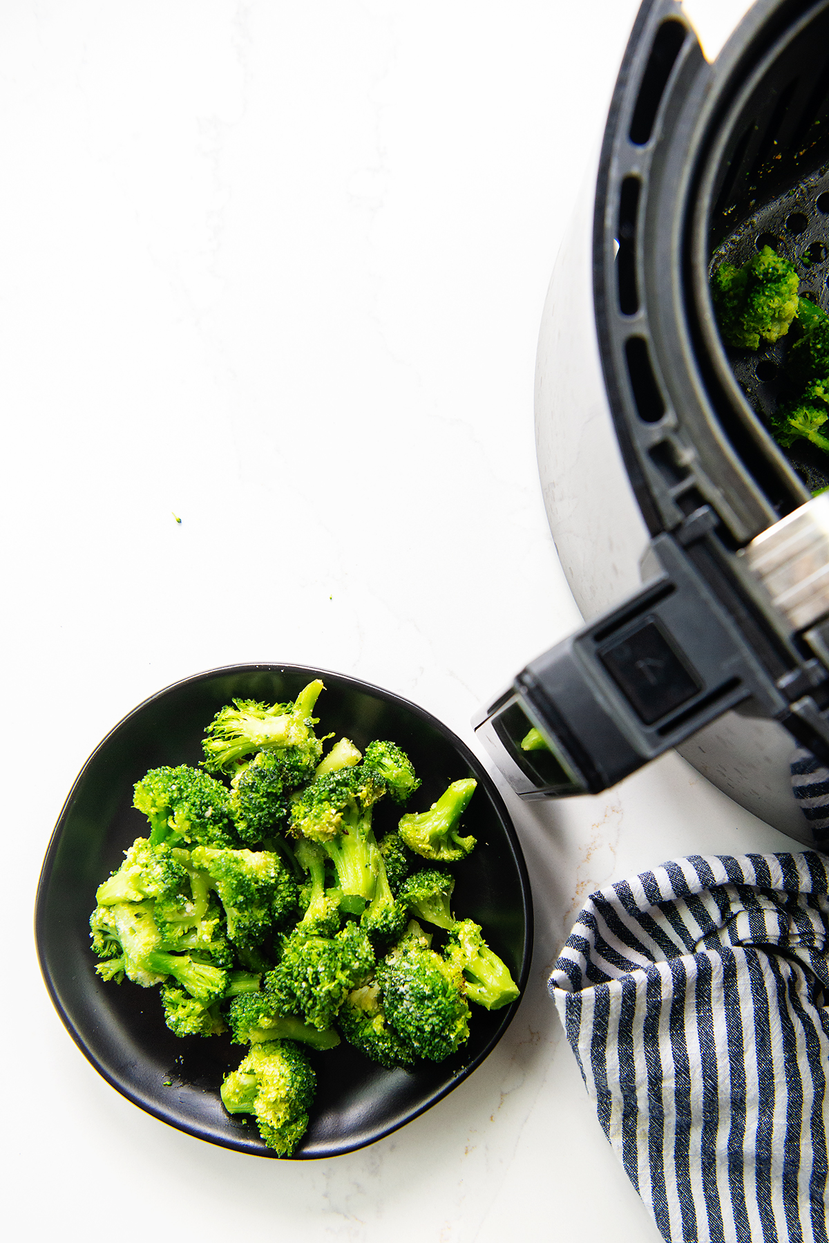Overhead view of broccoli on a small black plate next to an air fryer