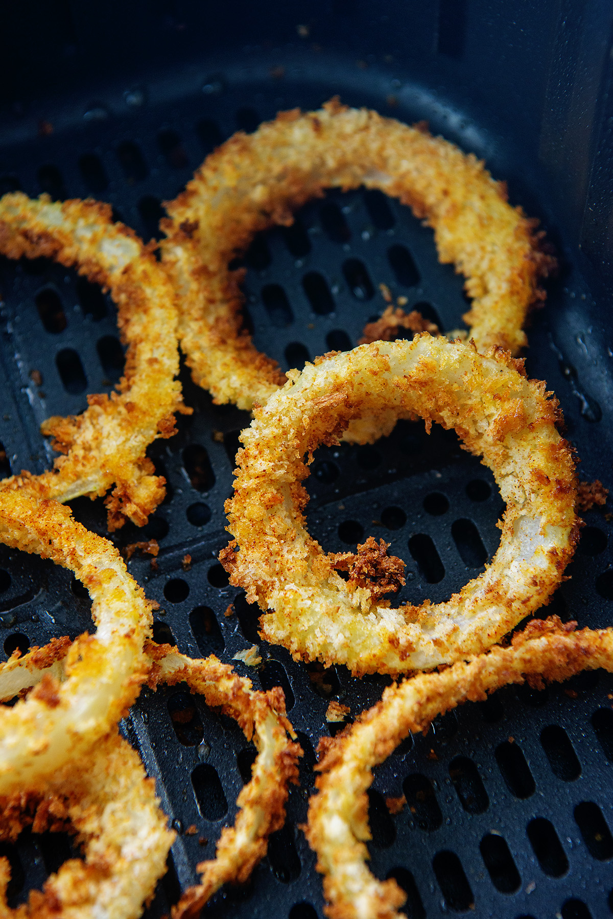 Close up of onion rings cooking in an air fryer