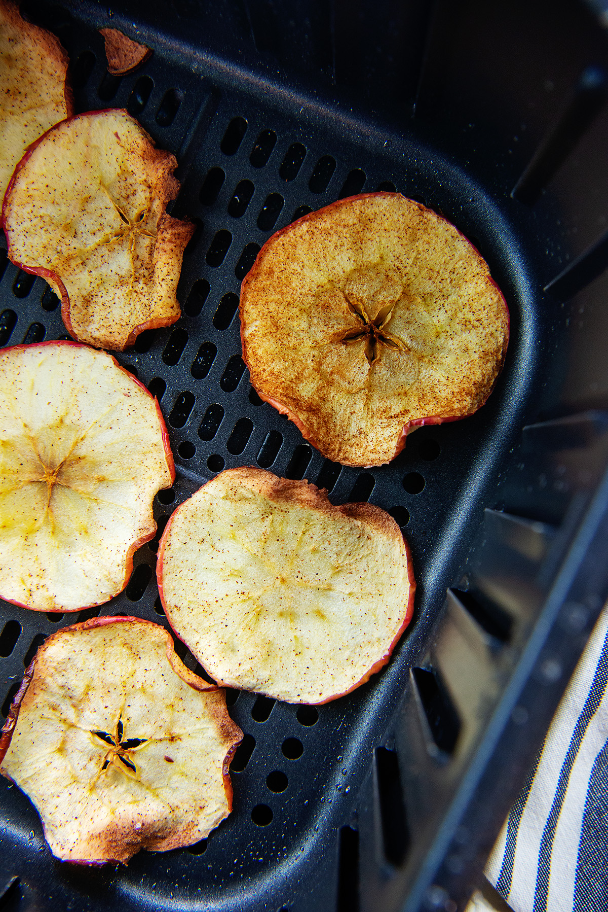 Cooked cinnamon apple chips in an air fryer basket