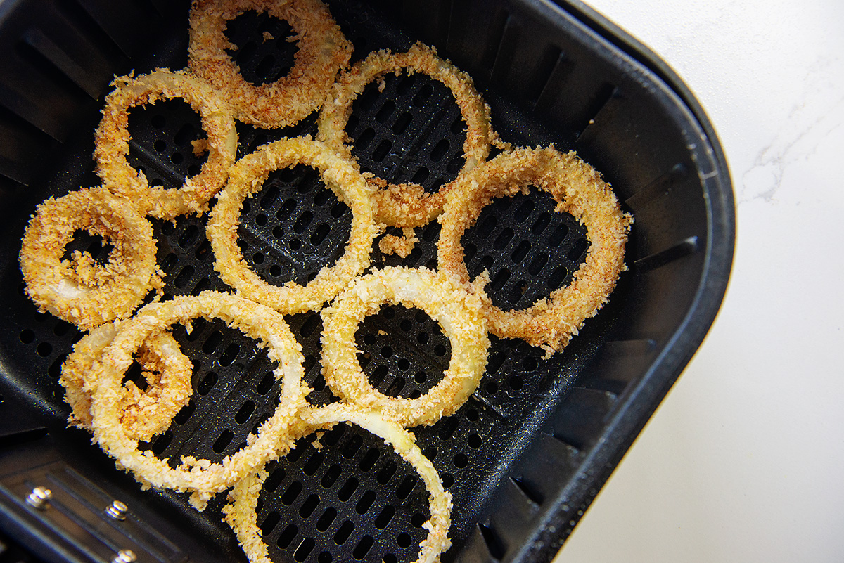 Coated raw onions in an air fryer basket