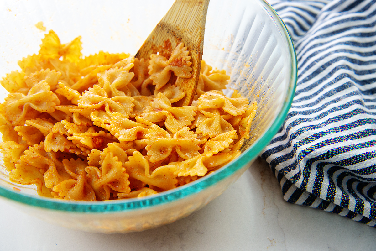cooked pasta in glass bowl with wing sauce.