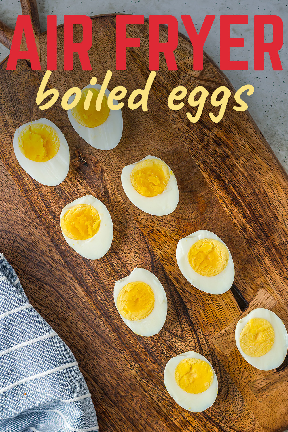 Overhead view of boiled eggs cut in half on a wooden serving tray