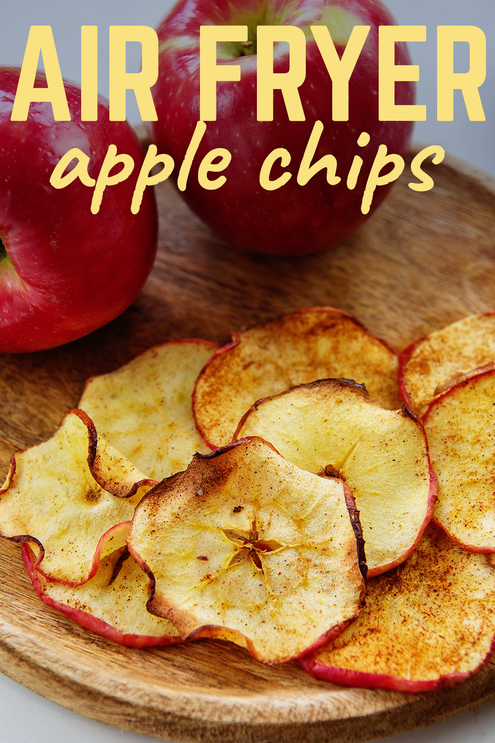 cooked apple chips on a plate in front of two apples
