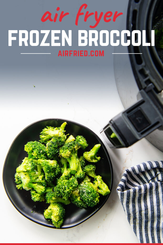 Overhead view of broccoli on a black plate next to an air fryer