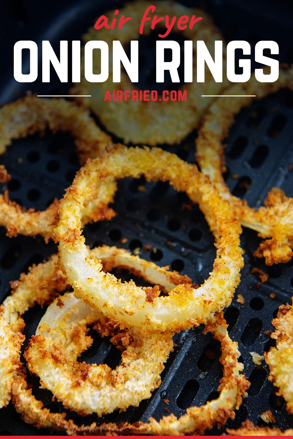 Close up of cooked onion rings in an air fryer basket