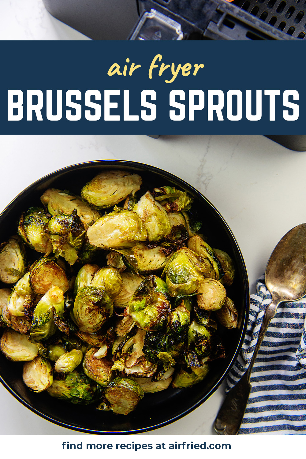Overhead view of brussels sprouts on a small black plate next to a spoon