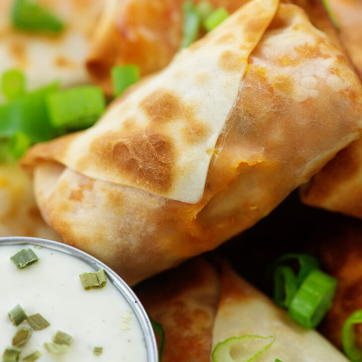 Close up of an egg roll next to ranch dressing