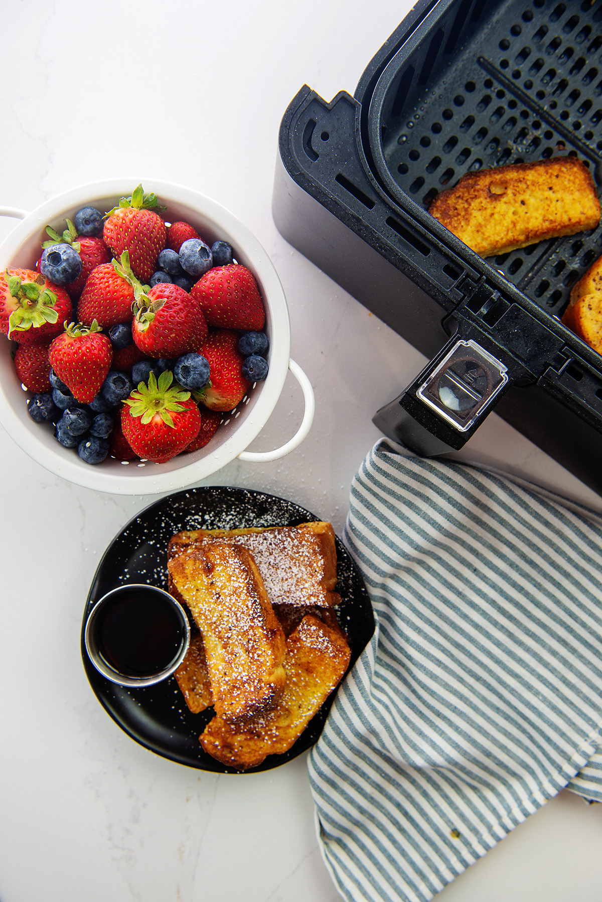 Overhead view of french toast, fruit, and an air fryer