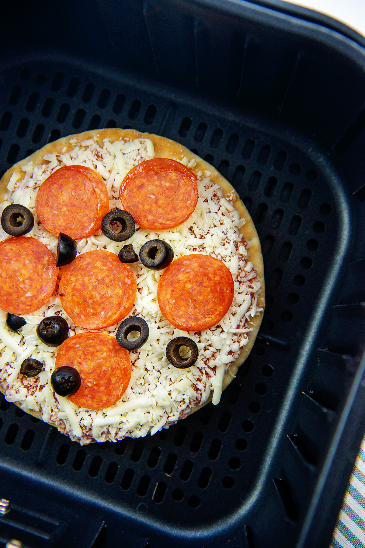 Overhead view of a raw pizza in an air fryer basket.