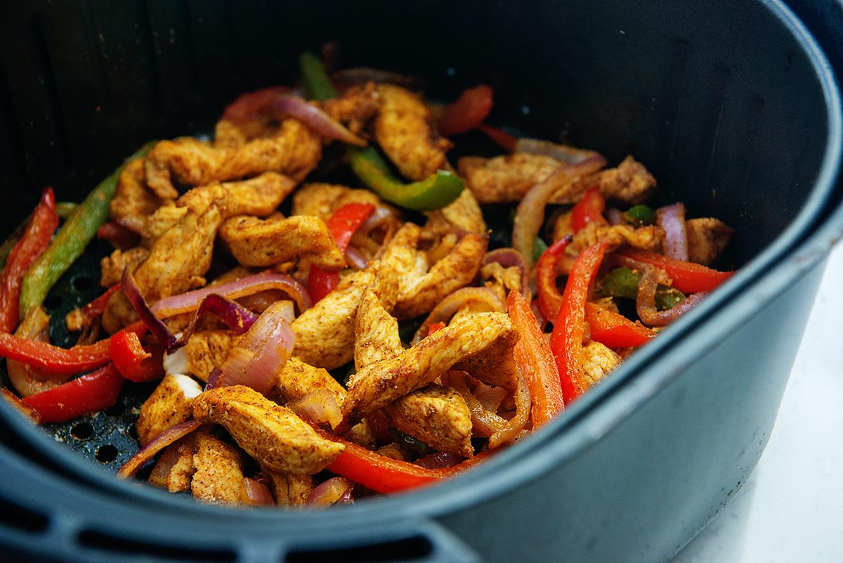 Seasoned and cooked chicken fajita ingredients in an air fryer basket