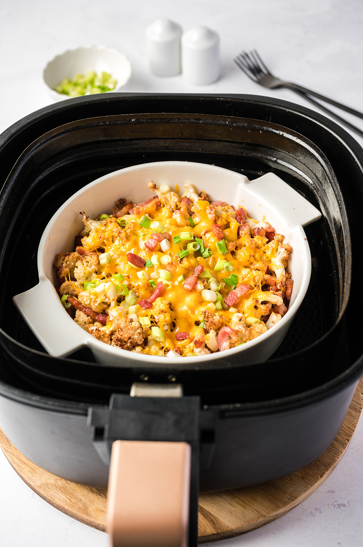 A baking dish of cauliflower and cheese in an air fryer basket