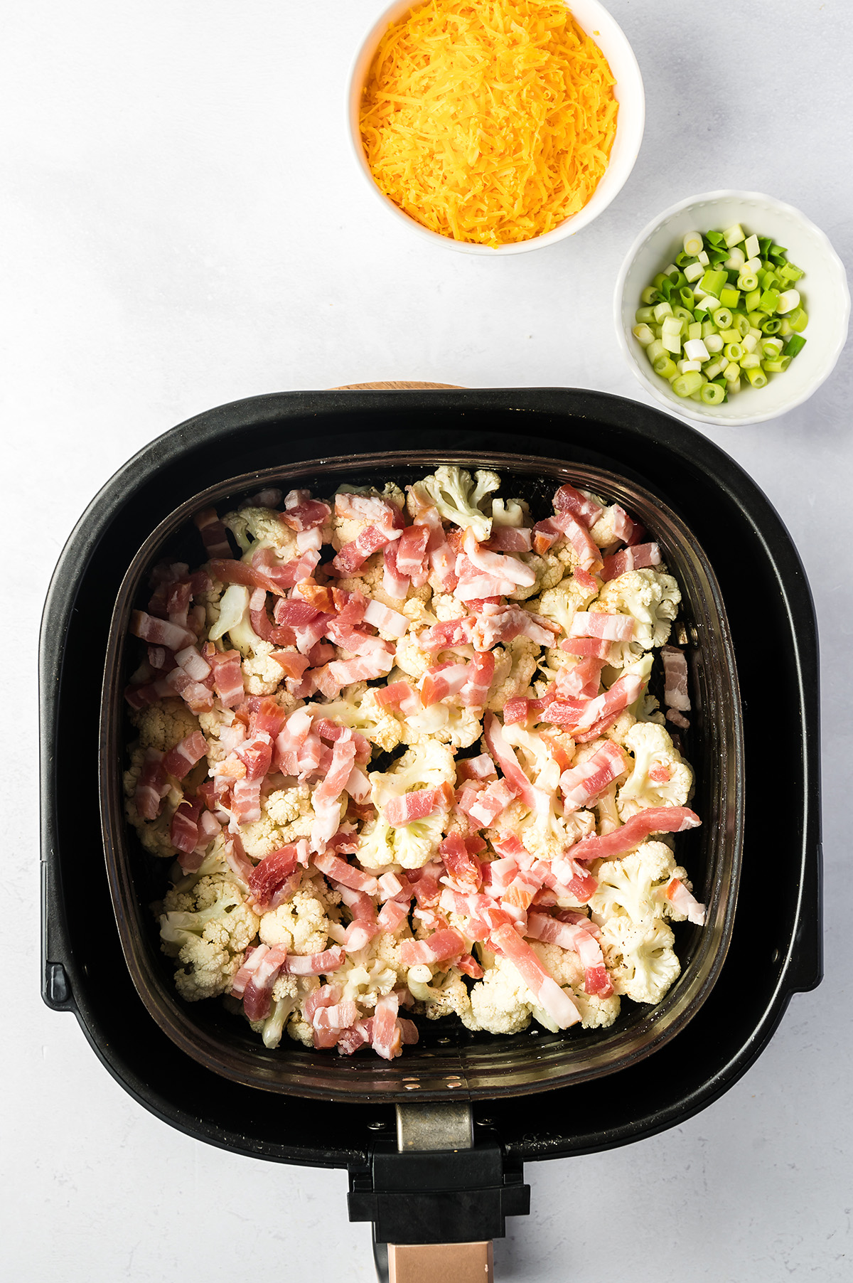 Raw bacon pieces on top of cauliflower in an air fryer basket