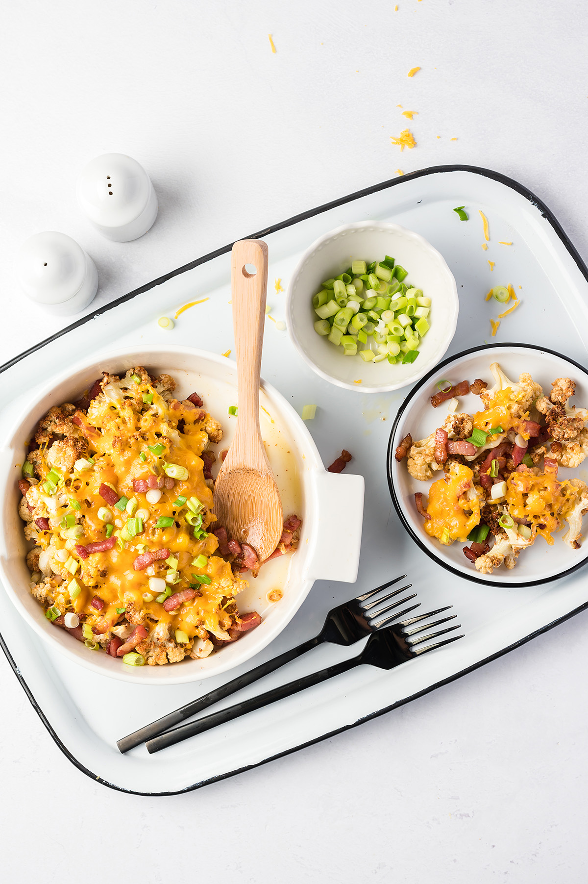 Overhead view of a serving tray with loaded cauliflower and two forks on it