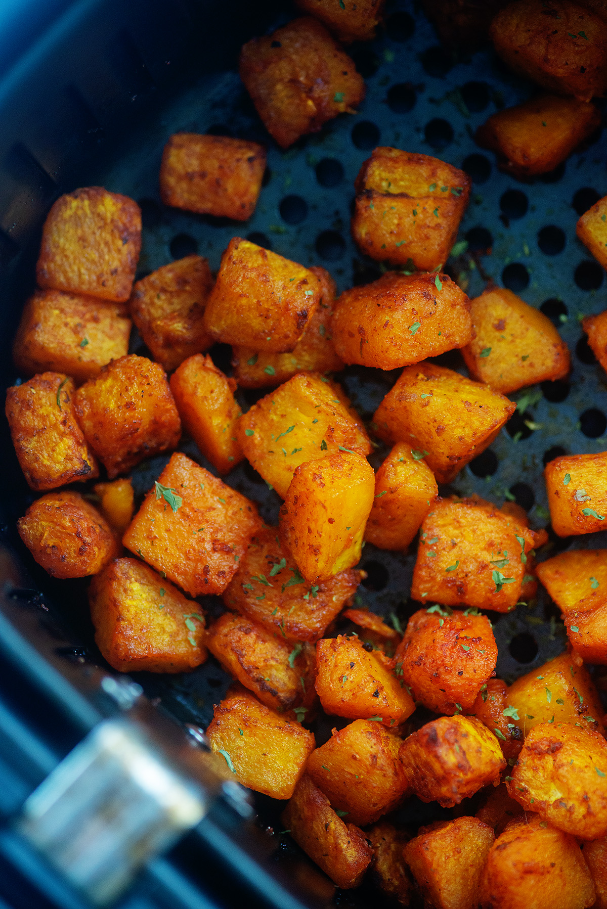 Close up of cooked cubes of butternut squash, seasoned.