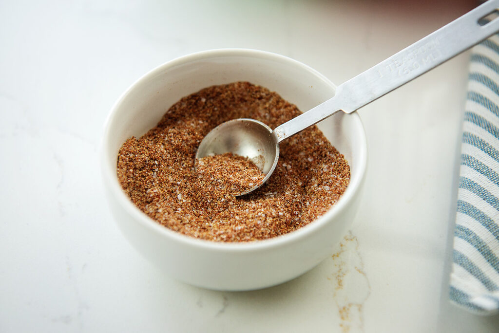 A measuring spoon in a dish of seasoning.