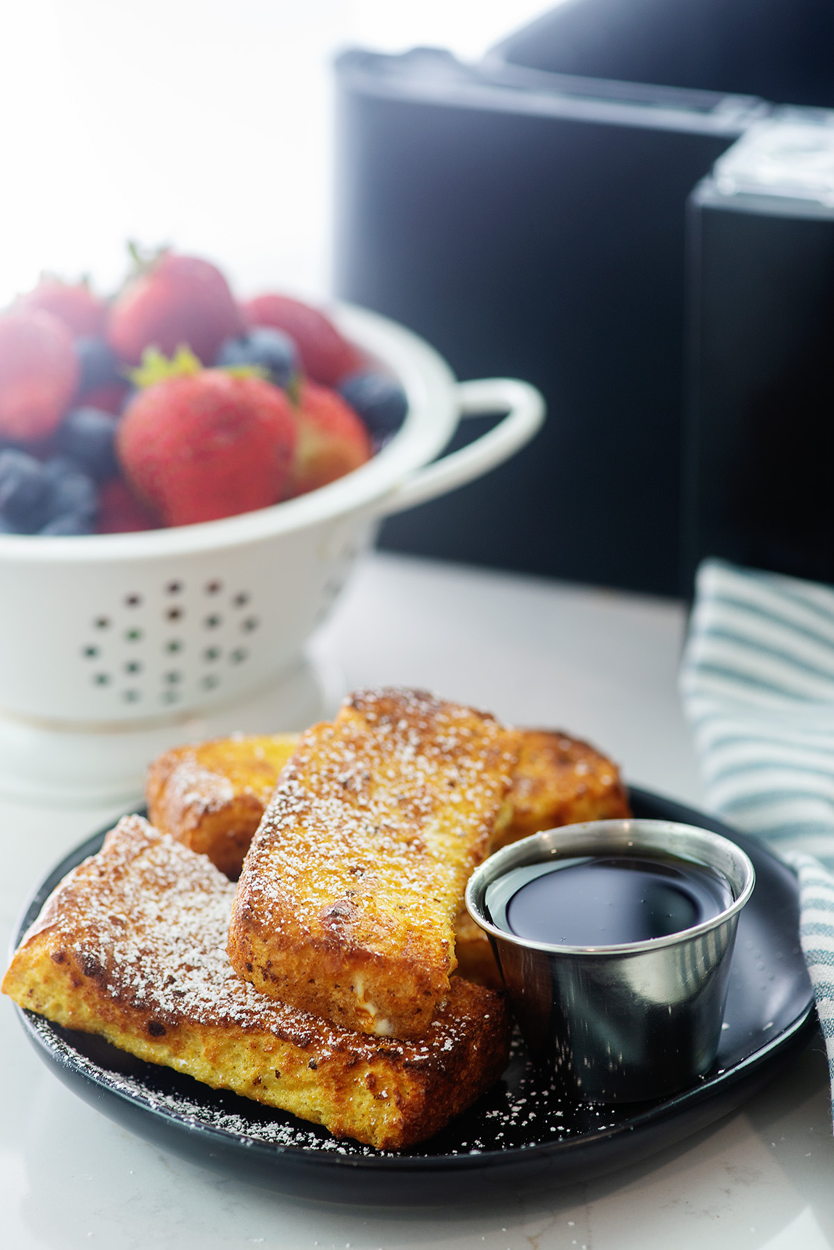Small black plate of French toast sticks in front of a bowl of fruit