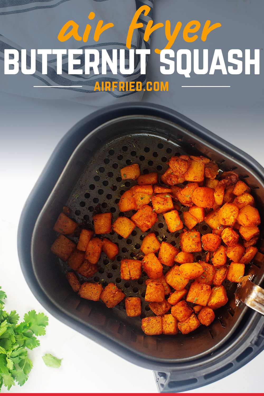 overhead view of cooked cubes of butternut squash in an air fryer