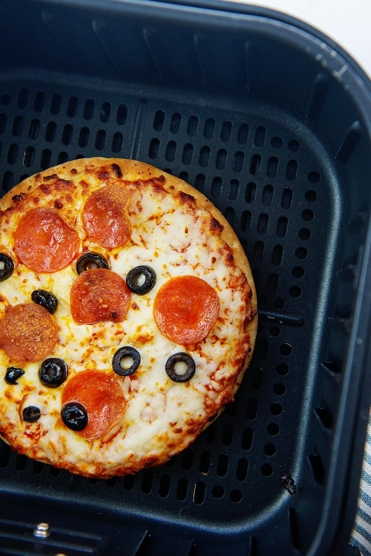 Frozen pizza in an air fryer basket