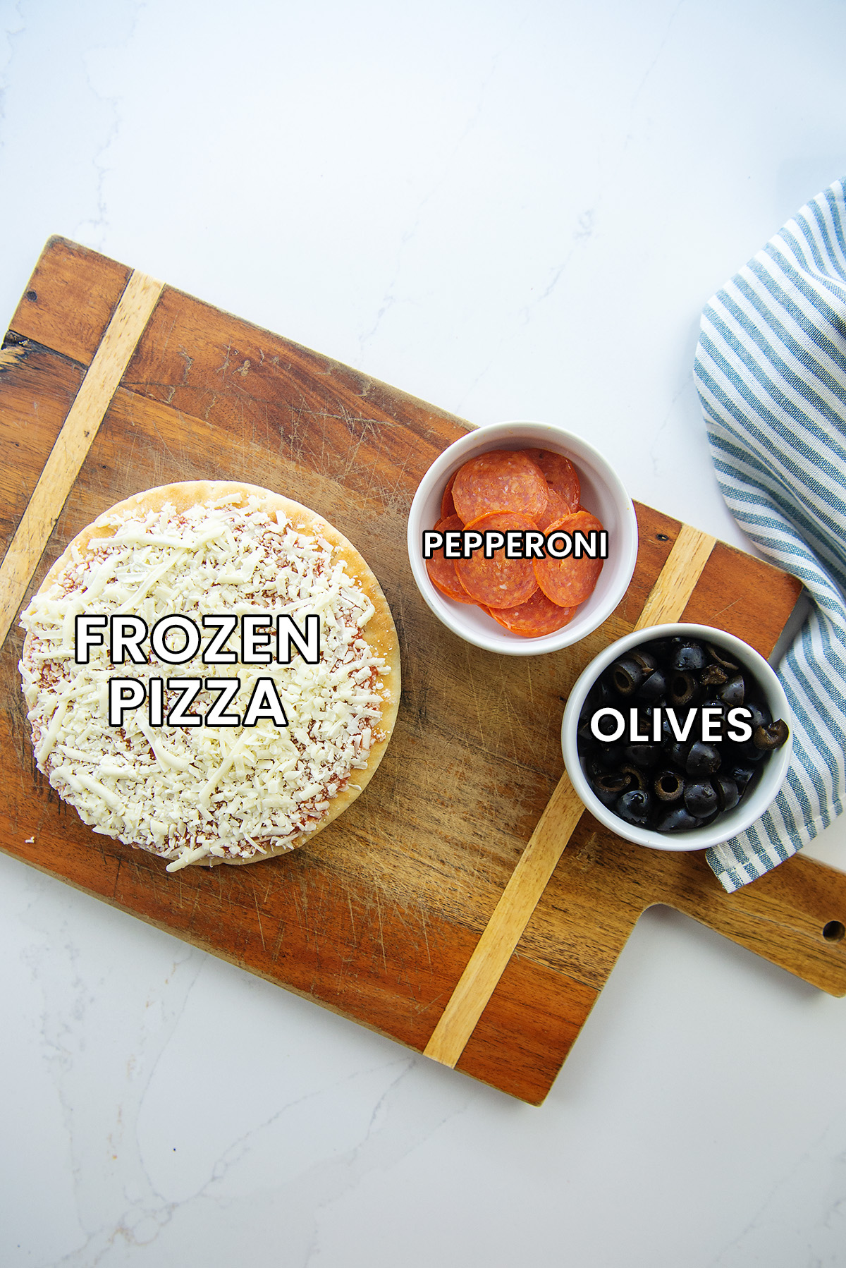 Frozen pizza, pepperoni, and black olives on a wooden cutting board.