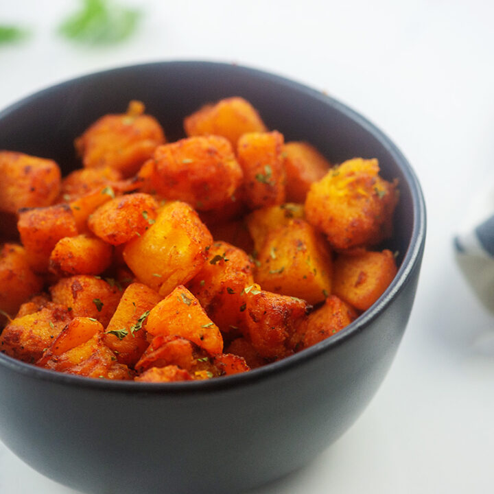 Cooked cubes of butternut squash in a black bowl