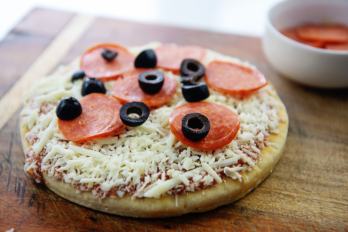Frozen pizza with pepperoni and olives on top