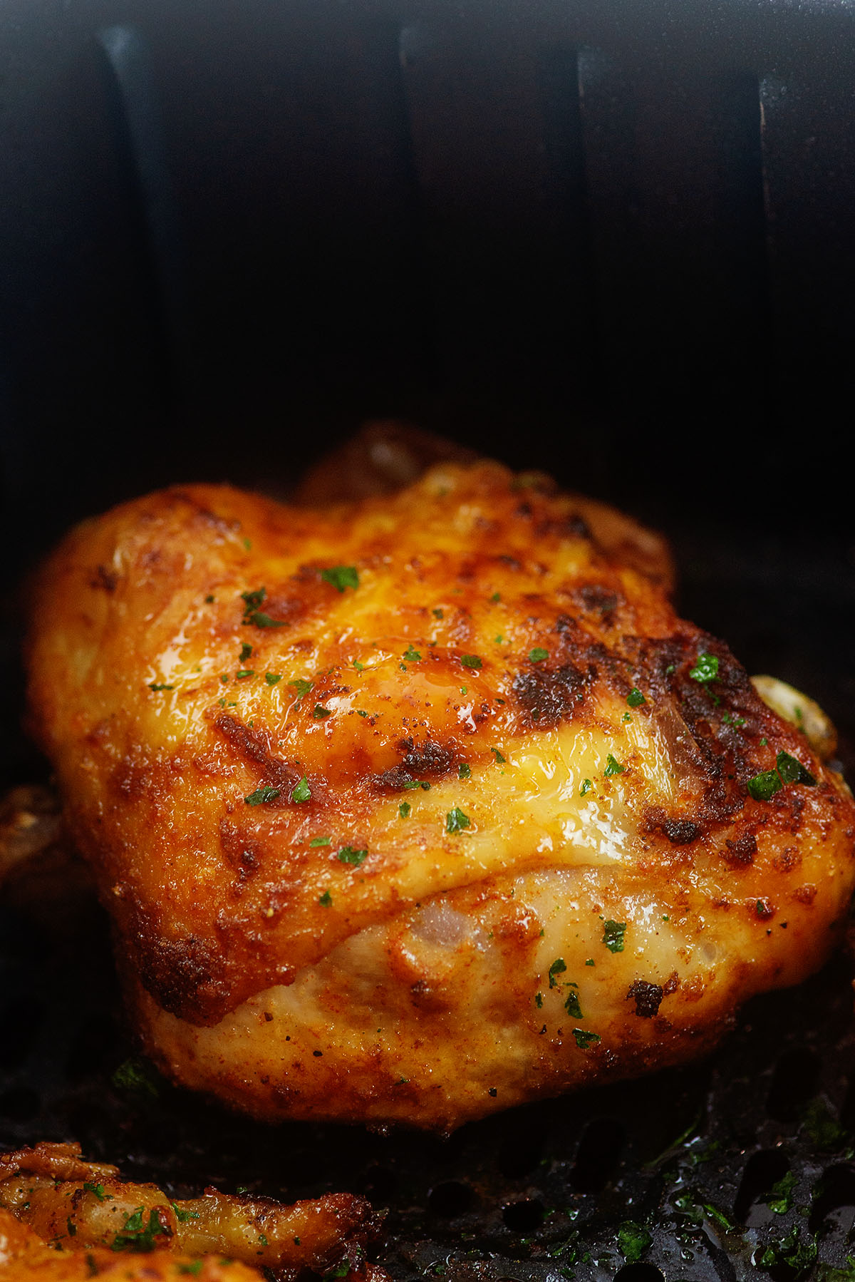 close up of cooked and seasoned chicken thigh in an air fryer basket.