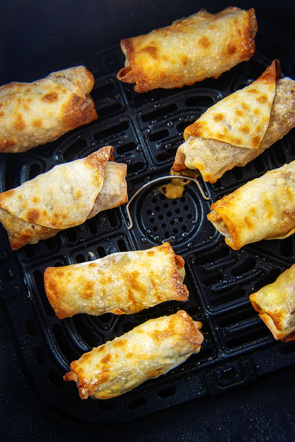 8 egg rolls cooked in an air fryer basket.