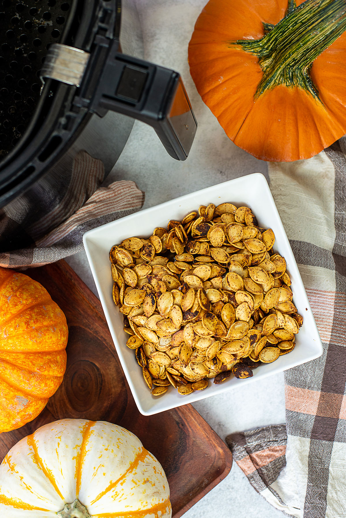 Overhead view of pumpkin seeds in a square white bowl.