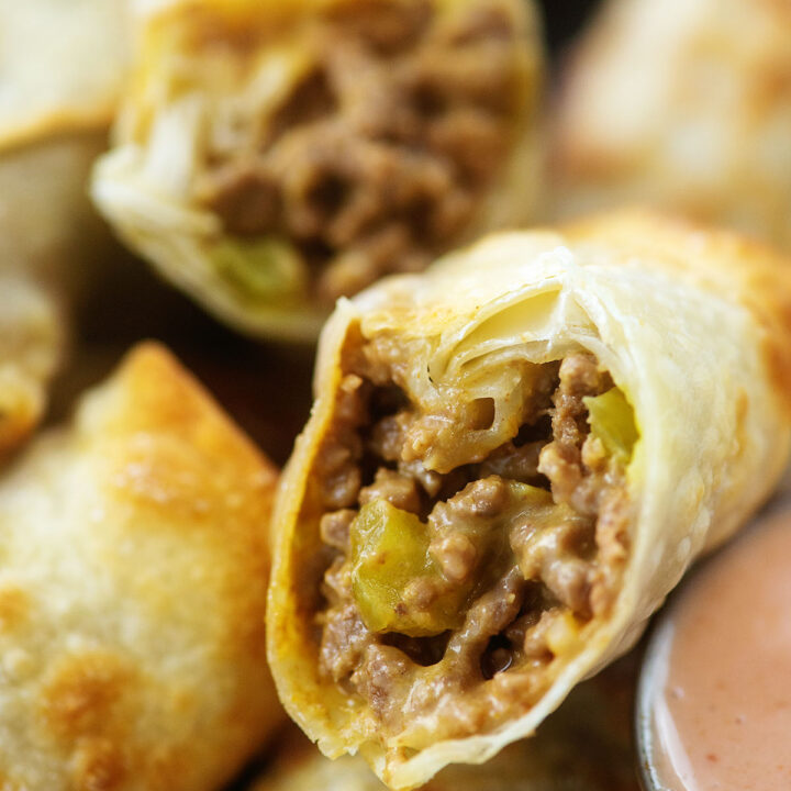 Cheeseburger egg rolls cut open to show the filling.
