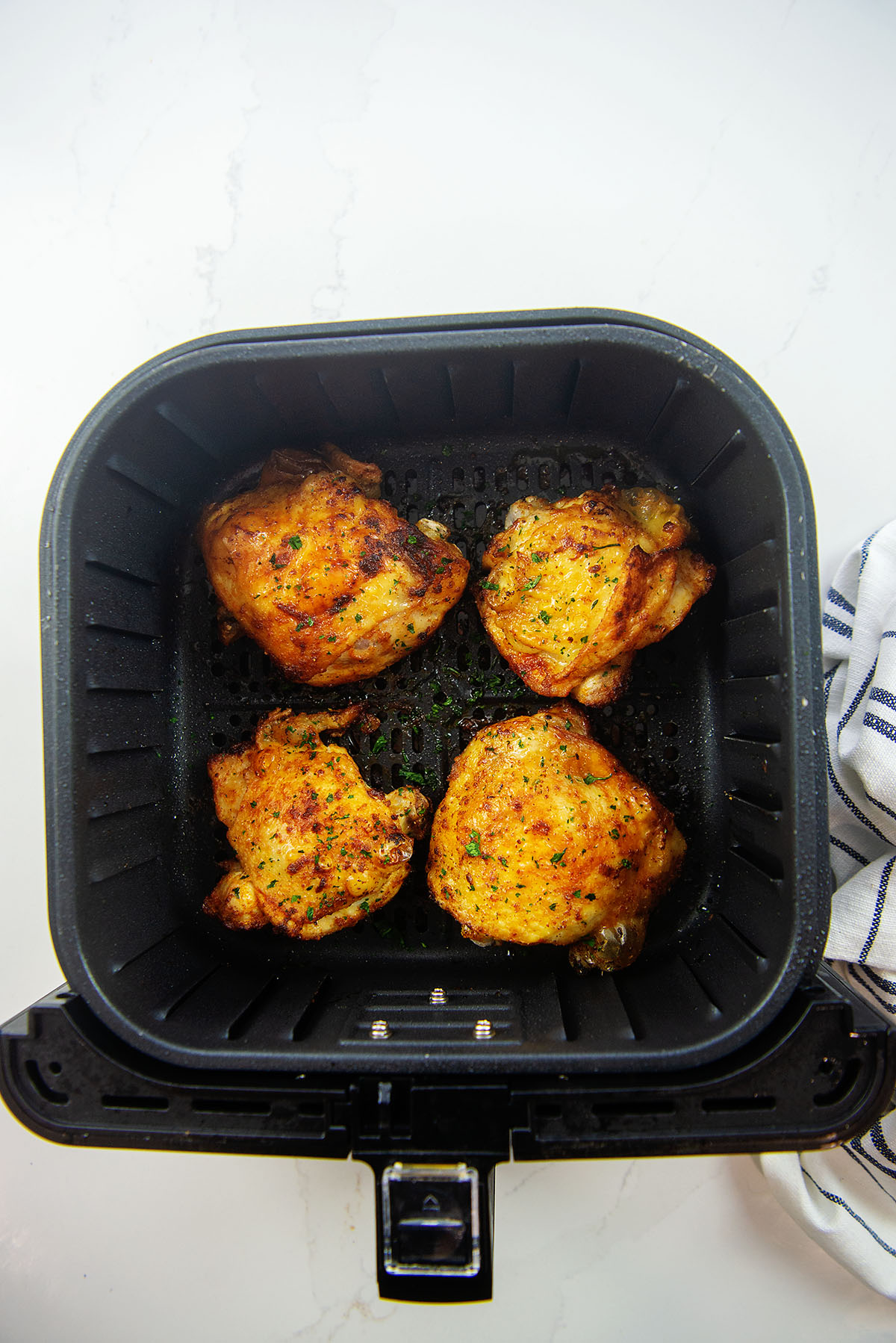 Overhead view of four chicken thighs in an air fryer basket on a white counter top.