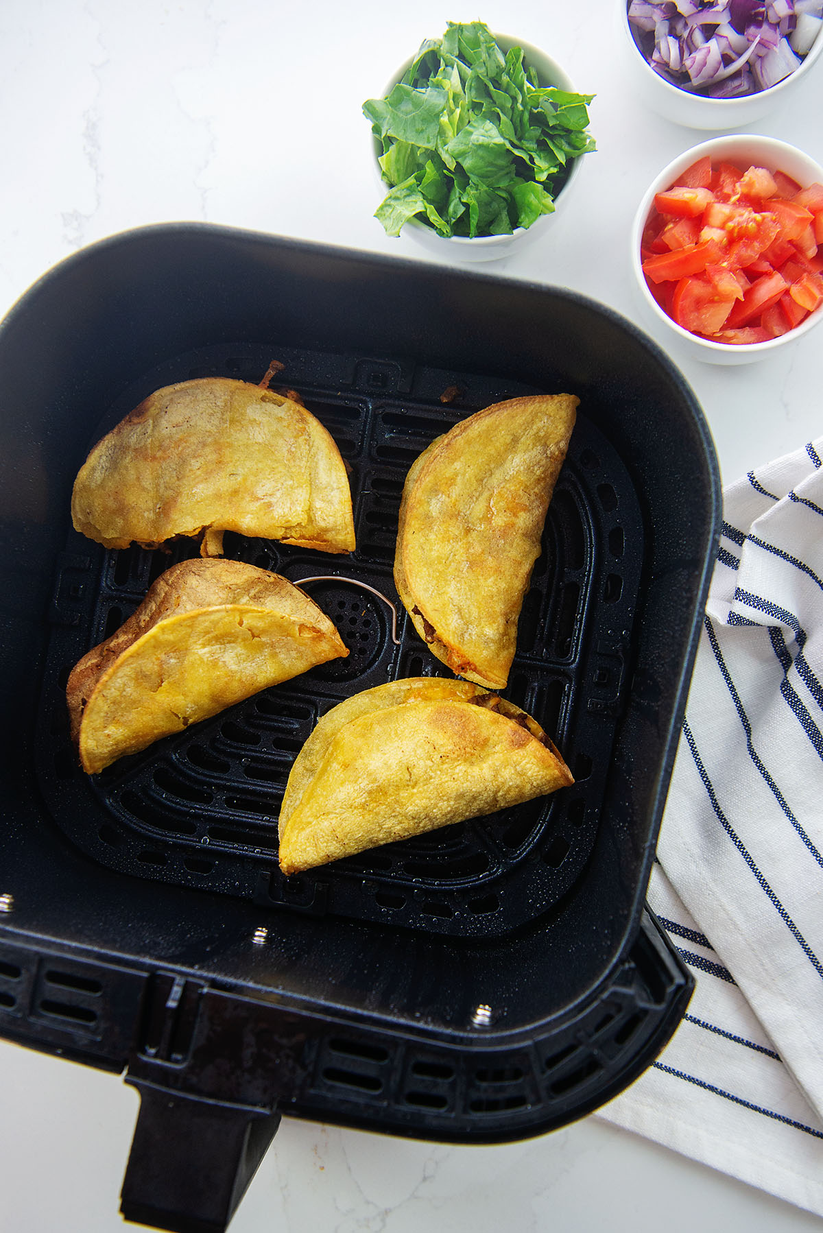 Overhead of four tacos in an air fryer basket.