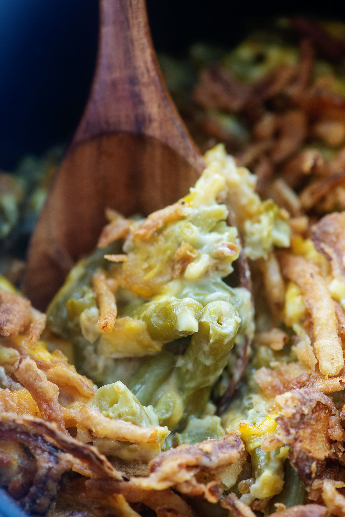 A wooden spoon dipping into green bean casserole