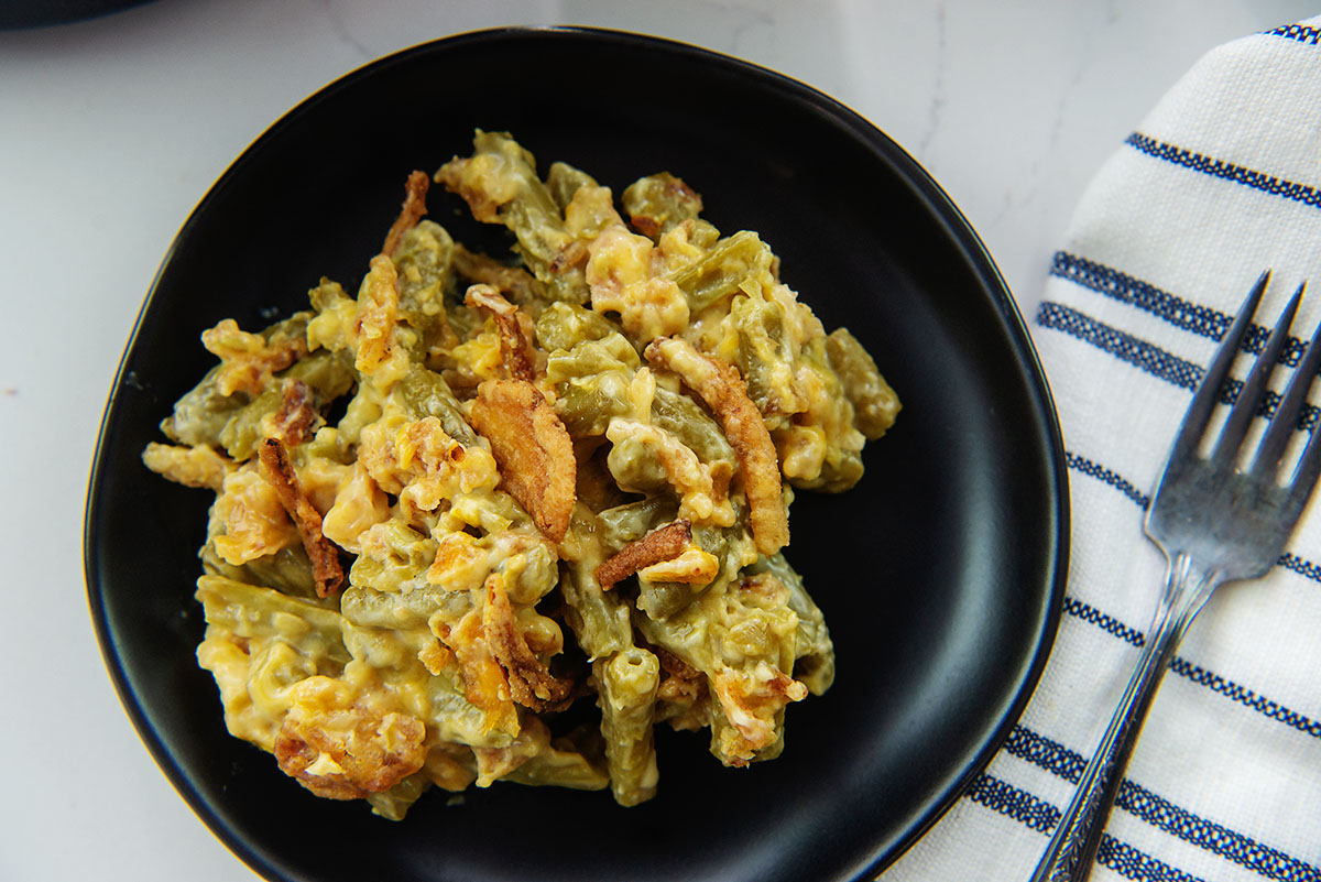 Close up of green bean casserole on a small black plate