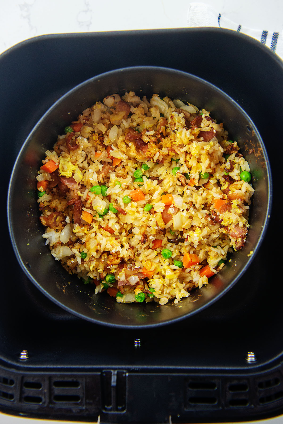 Overhead view of fried rice in a baking dish in an air fryer basket