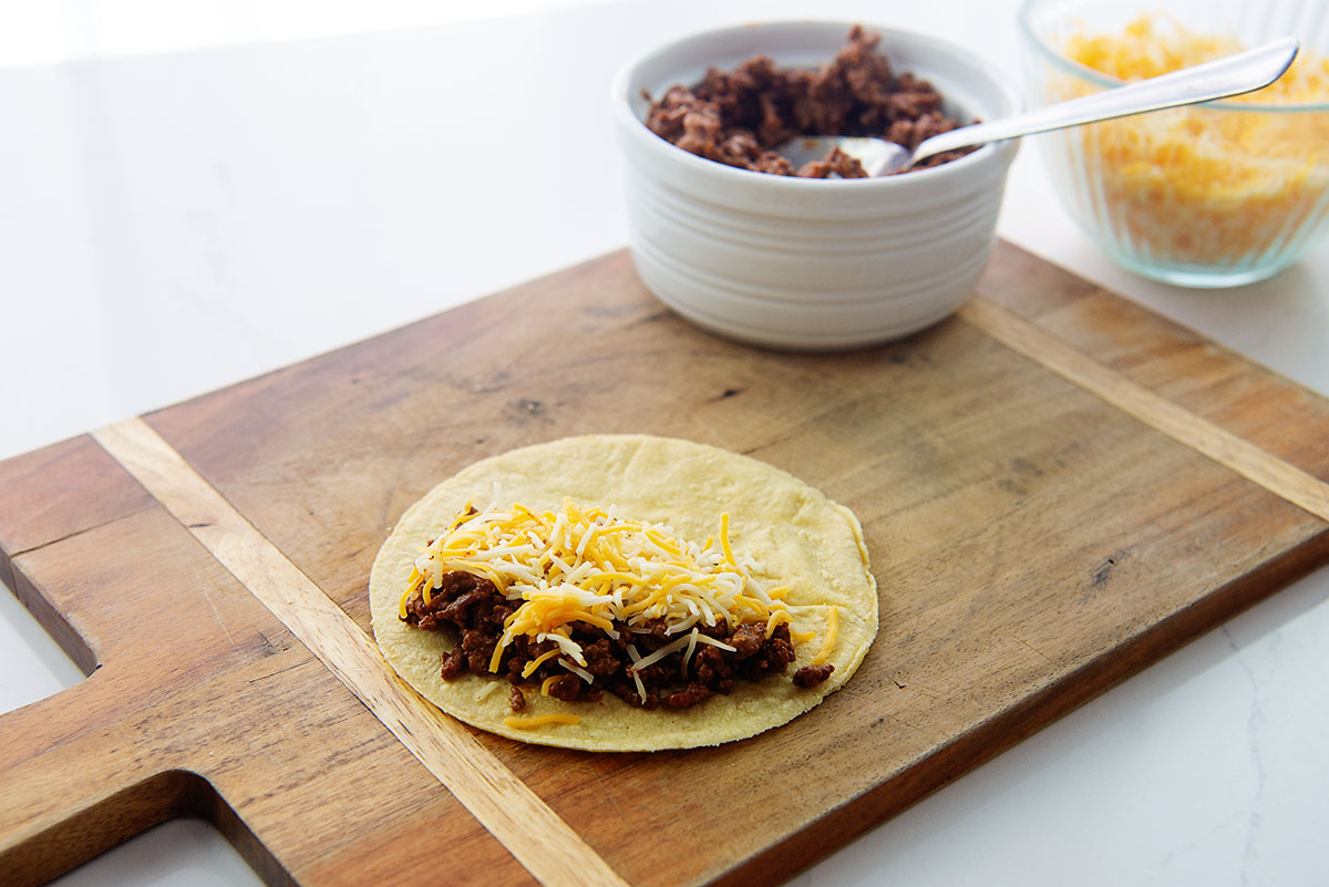 Open face taco on a wooden cutting board