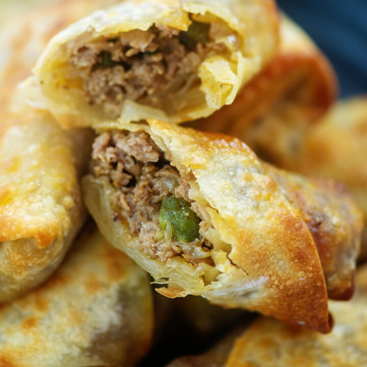 stacked philly cheese steak egg rolls with the one on top spilt open