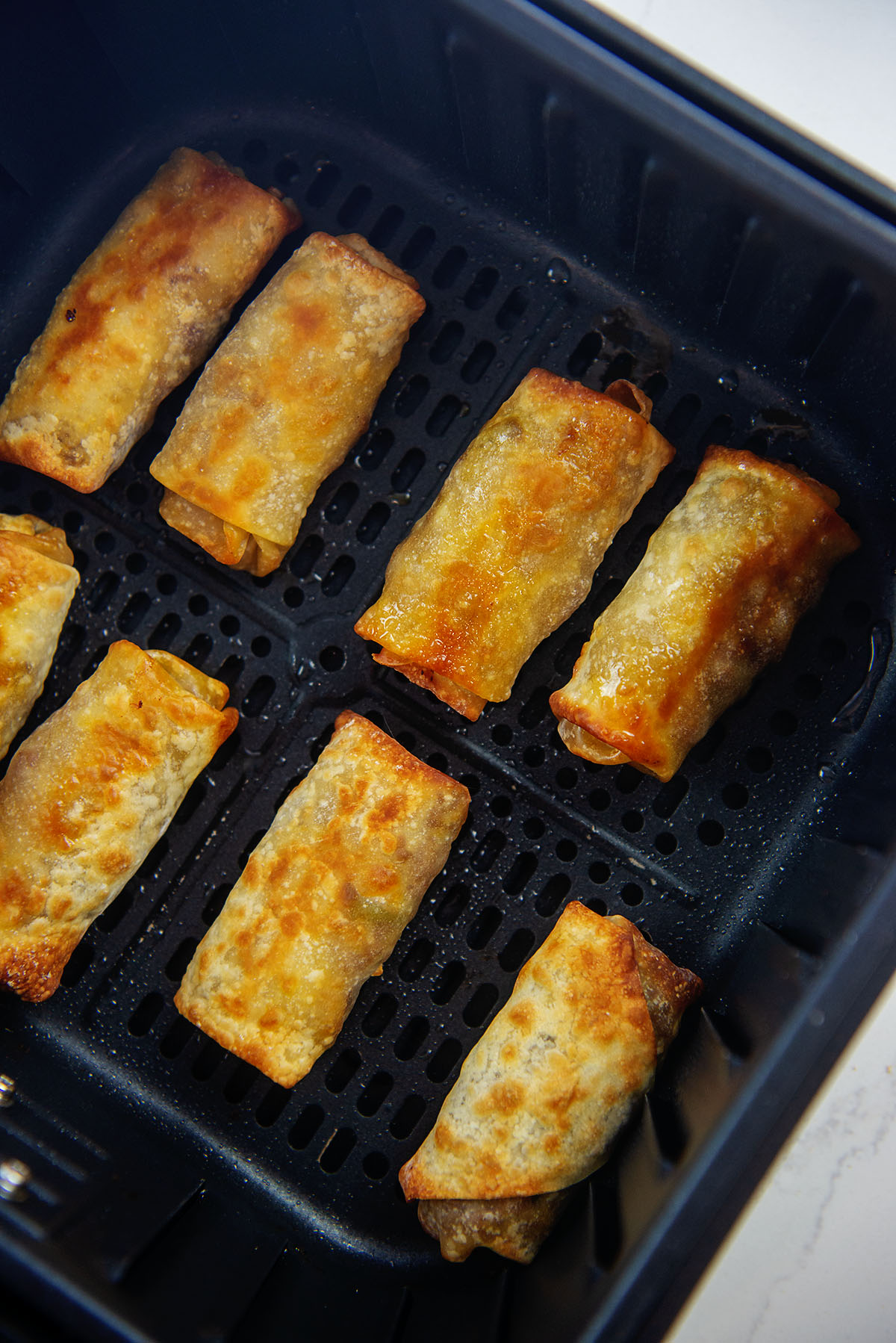 Eight egg rolls lined up in an air fryer basket