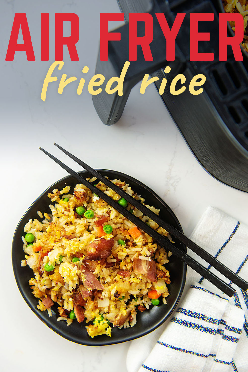 An air fryer next to a plate of fried rice.